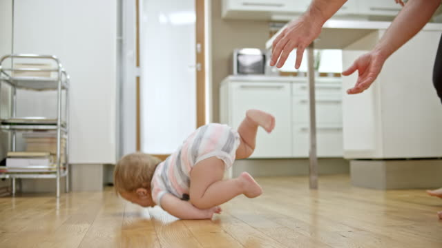 slo mo baby boy tipping over and falling - primi passi video stock e b–roll