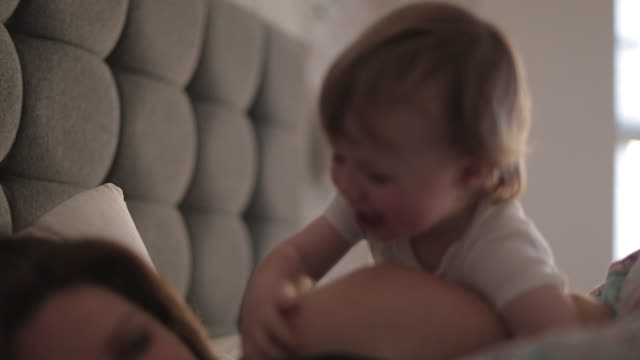 baby boy waking up his mother - aufwachen stock-videos und b-roll-filmmaterial