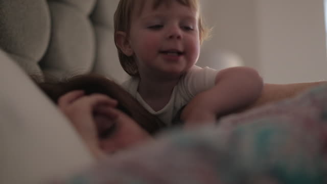 stockvideo's en b-roll-footage met baby boy waking up his mother - differential focus
