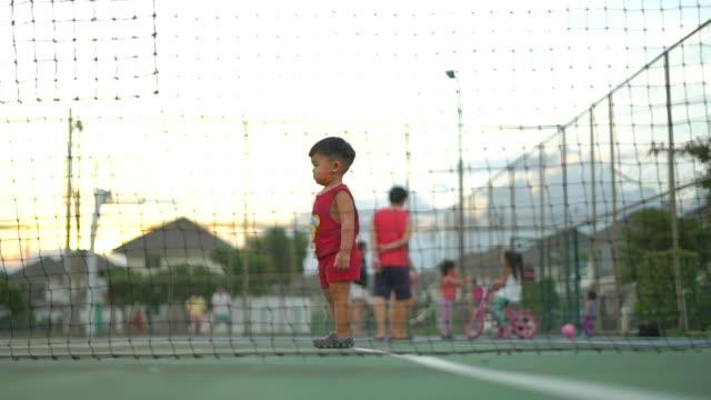 vídeos y material grabado en eventos de stock de bebé caminando en la cancha de tenis por la noche - cubo recipiente