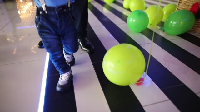 baby boy walking while holding fathers hand - bretella video stock e b–roll