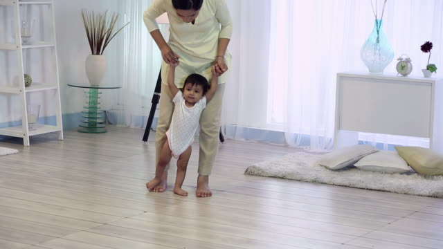 Baby boy walking with the help of mother