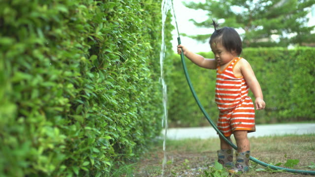 baby boy watering plants with green rubber strap in the garden at summer sunny day. - toddler stock videos & royalty-free footage