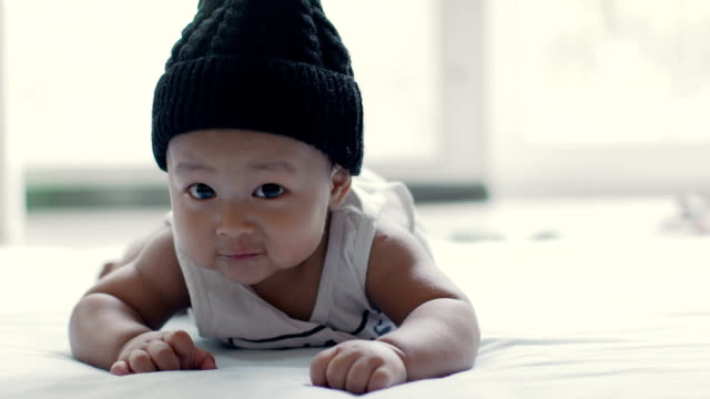 Baby boy (6-9 months) wear hat with crawling on the mat