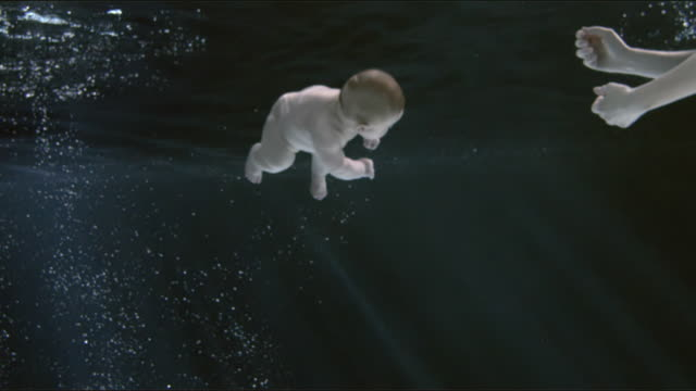 ms slo mo tu baby boy (2-5 months) with woman floating underwater surface / london, united kingdom - baby boys stock videos and b-roll footage