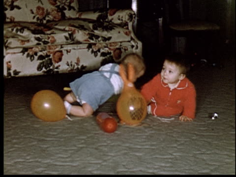 stockvideo's en b-roll-footage met 1955 ms baby boys crawling on floor playing with balloons - prelinger archief