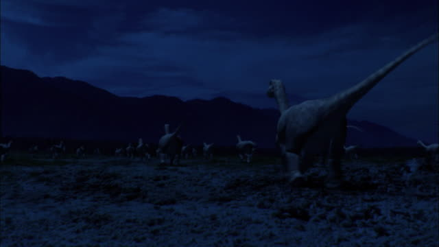 stockvideo's en b-roll-footage met cgi, ms, baby brontosauruses running through field at night, rear view - jura mesozoïcum