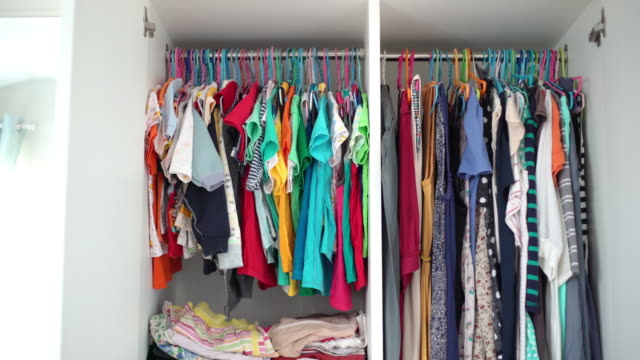 baby clothes and woman clothes hanging in wardrobe at home - tidy stock videos & royalty-free footage