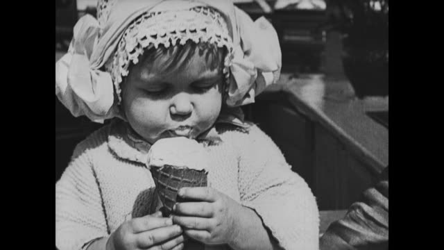 1917 baby contentedly eats ice-cream at ice-cream stand at coney island - ice cream cone stock videos & royalty-free footage