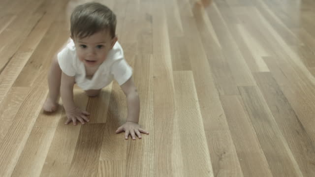 a baby crawling across a wooden floor wearing a onesie - krabbeln stock-videos und b-roll-filmmaterial