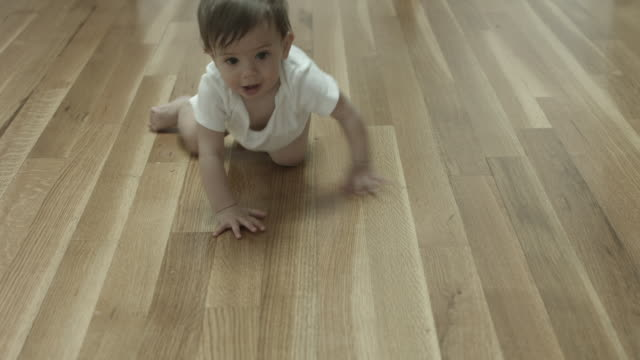 A baby crawling across a wooden floor wearing a onesie