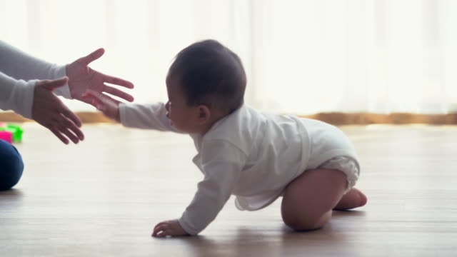 vídeos de stock, filmes e b-roll de ms baby crawling across the floor to her mother - engatinhando