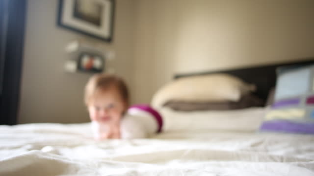 a baby crawling towards the camera with her toys and games around her. - babies only stock videos & royalty-free footage