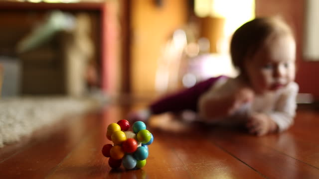 a baby crawling towards the camera with her toys and games around her. - crawling stock videos & royalty-free footage