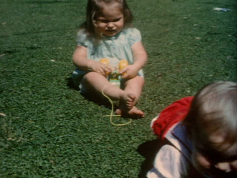 a baby crawls across a lawn and her sister tries to help her walk. - crawling stock videos & royalty-free footage
