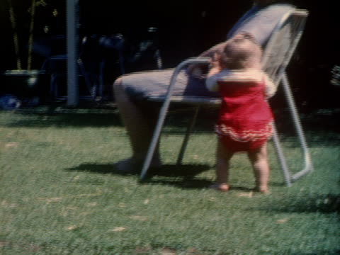 a baby crawls around a lawn, tries to stand by a lawn chair and crawls away. - krypa bildbanksvideor och videomaterial från bakom kulisserna