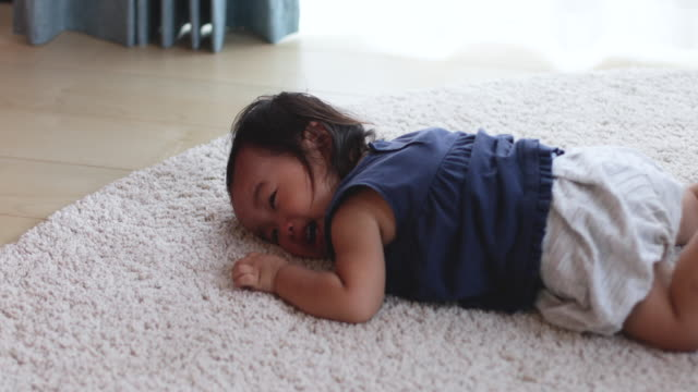 baby crying at her lie on her face. - face down stock videos & royalty-free footage