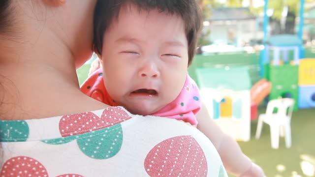 母親の抱擁で泣いている赤ちゃん。 - 泣く点の映像素材/bロール