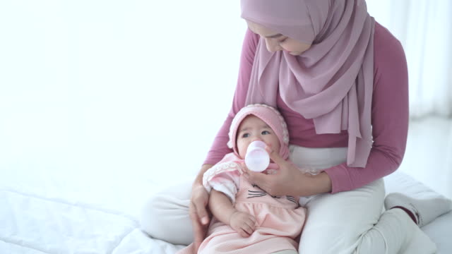 baby cute girl drinking bottle milk on the bed - milk bottle stock videos & royalty-free footage
