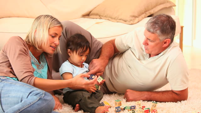 baby discovering blocks with his parents / cape town, western cape, south africa - 横向きに寝る点の映像素材/bロール