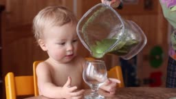 Baby drinks fresh green smoothie from wineglass. Healthy vegan/raw lifestyle. Mother fills wineglass.