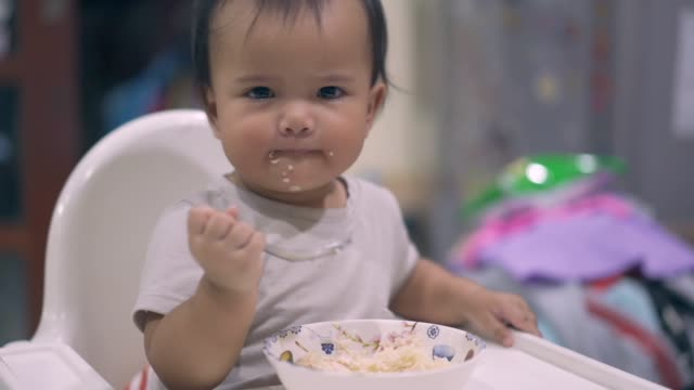 baby eating baby food sitting on the high chair - only baby girls stock videos & royalty-free footage