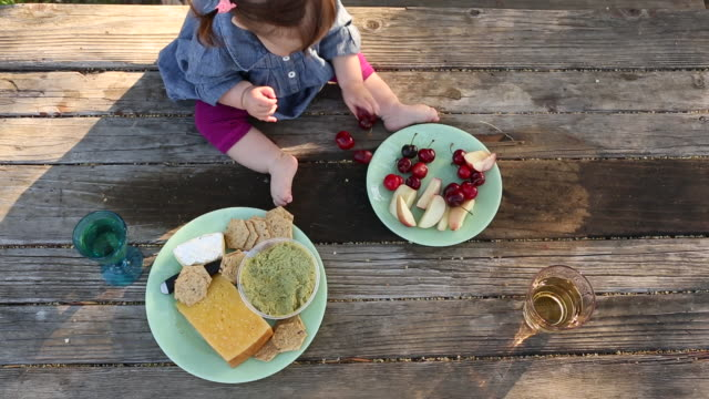 a baby eating from a plate of fruit outside on a picnic table. - picnic table stock videos & royalty-free footage
