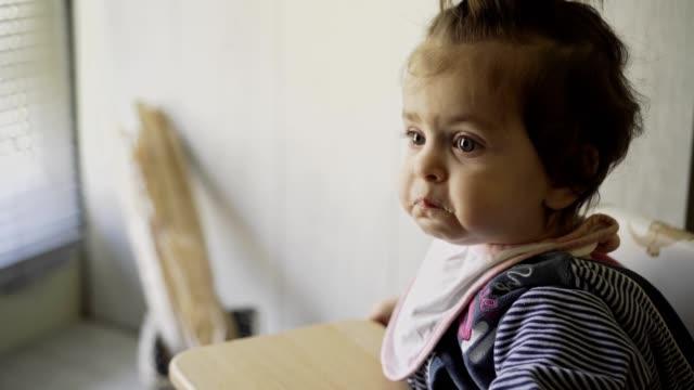 vídeos de stock, filmes e b-roll de bebê que come na cadeira de alimentação. vídeo stock - comida de bebê