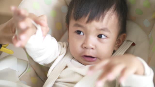 slo mo baby eating in feeding chair - soltanto un neonato maschio video stock e b–roll