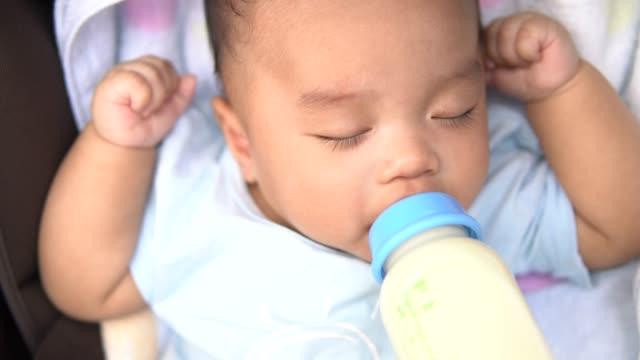 vídeos y material grabado en eventos de stock de bebé comiendo leche de botella en la silla de paseo - 6 11 meses