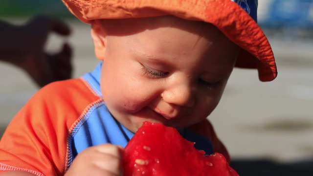 Baby Eating watermelon. Vibrant Red and Orange