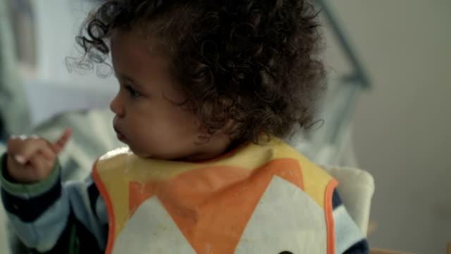 vídeos de stock, filmes e b-roll de hd: bebê apreciando uma colher de alimentos - cadeirinha cadeira