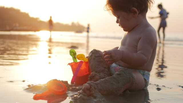 Baby enjoying sunset at the beach in summer by playing with toys in the sand