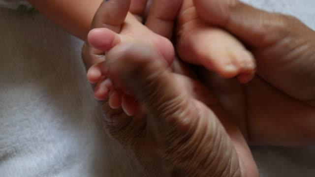 De voeten van de baby in handen van de moeder. Pasgeboren Baby's voeten op vrouw