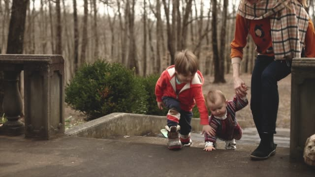 baby first steps holding hands with sibling and mother outdoors climbing stairs - warm clothing stock videos & royalty-free footage