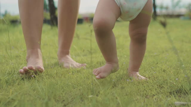 baby first steps on grass with her mother - first steps stock videos & royalty-free footage