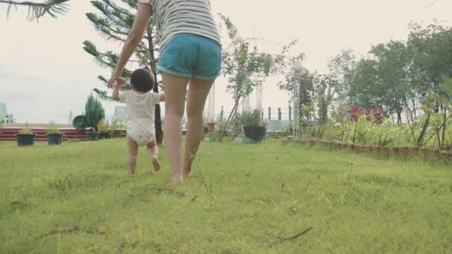 vídeos de stock, filmes e b-roll de primeiros passos de bebê na grama com a mãe dela - primeiros passos