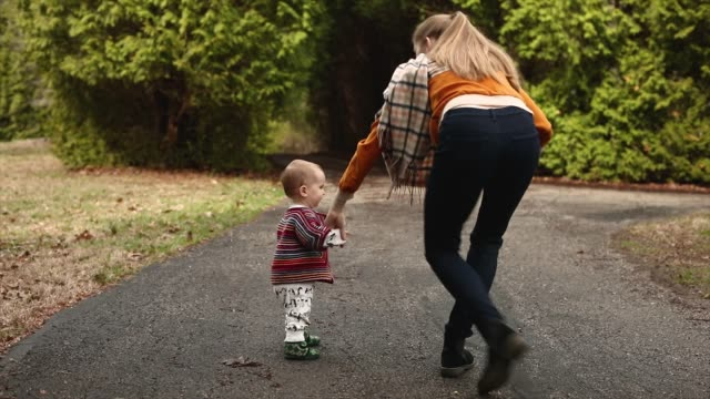 baby first steps walking away outdoors holding hands with mother - warm clothing stock videos & royalty-free footage