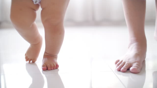 slow motion : baby first steps with mother and assisted walking - neonate video stock e b–roll