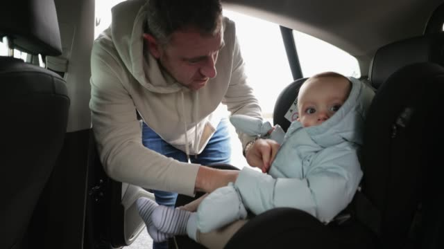 vídeos de stock e filmes b-roll de baby getting strapped into the car - domingo