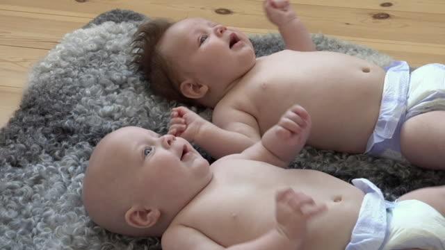 vídeos de stock e filmes b-roll de cu baby girl (6-11 months) and baby boy (2-5 months) lying on rug / gavle, gavleborg county, sweden - 2 5 meses