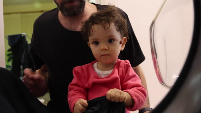 baby girl and her father put their clothes in the washing machine - utensil stock videos & royalty-free footage
