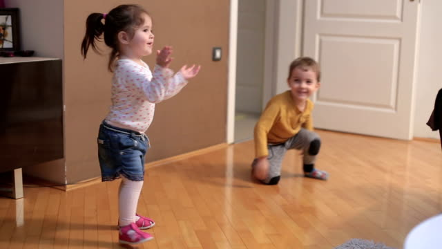 baby girl and toddler boy spinning and playing in the living room - 2 3 years stock videos & royalty-free footage
