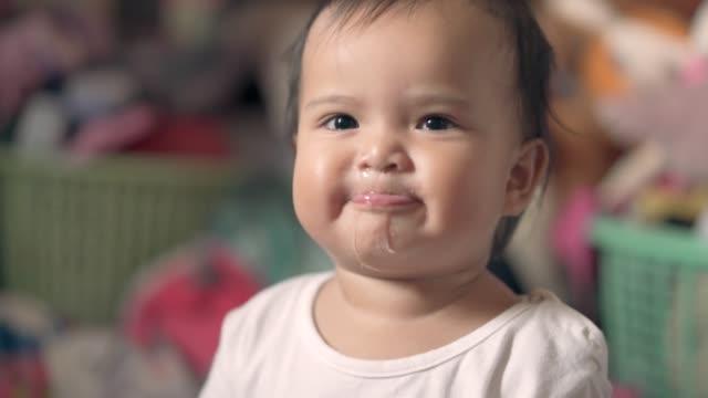 vídeos y material grabado en eventos de stock de niña soplando saliva y sonriendo - soplar
