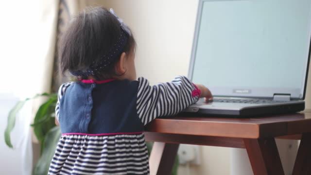 vídeos de stock, filmes e b-roll de teclado de computador portátil do bebê menina quebra - teclado de computador