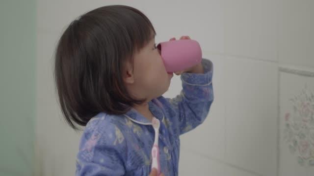 女の赤ちゃんが自分で歯を磨く - お手洗い点の映像素材/bロール
