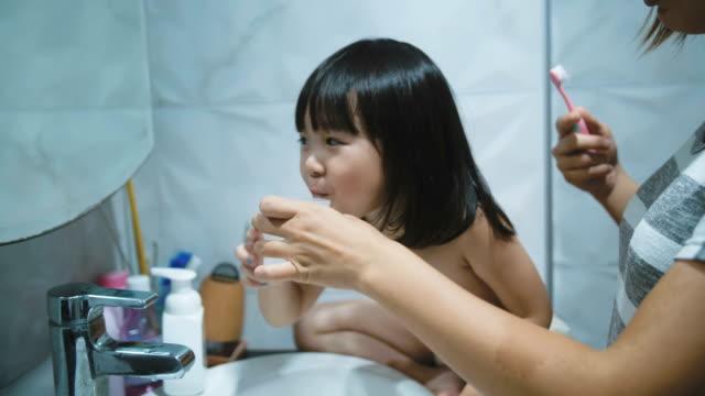 vídeos de stock, filmes e b-roll de menina escovando os dentes sozinha - escovar dentes