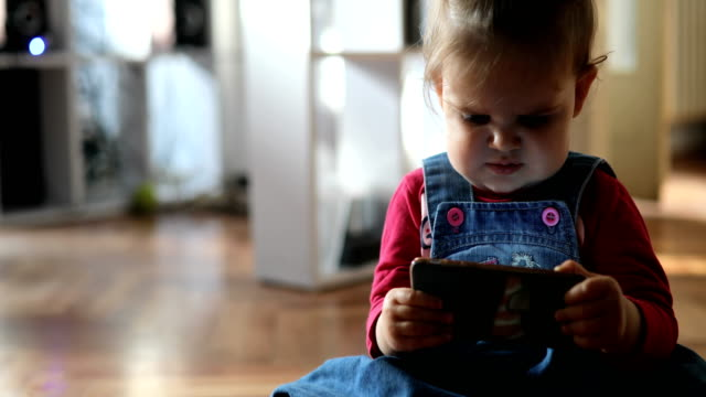 stockvideo's en b-roll-footage met baby meisje kauwen telefoon - kauwen
