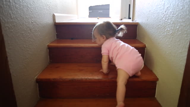 vídeos de stock, filmes e b-roll de a baby girl climbing up and playing at the top of a small set of stairs indoors. - escadaria