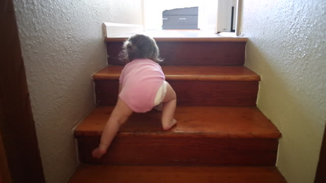 A baby girl climbing up and playing at the top of a small set of stairs indoors.